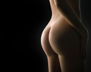Beautiful ass of young woman over dark background